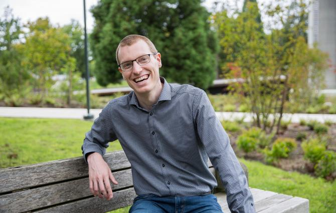 Prof Zachary Hudson sitting on a bench at UBC Vancouver