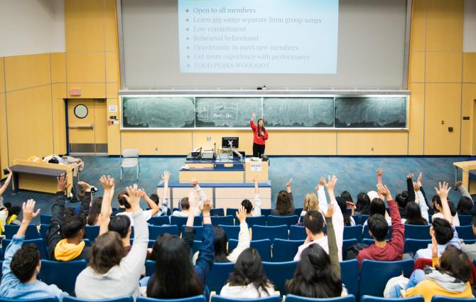 Students raising their hands in a lecture hall