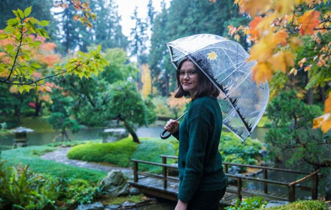 A student is taking a walk in a garden on a rainy fall day