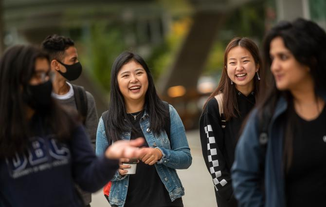 Group of students walking and talking on campus
