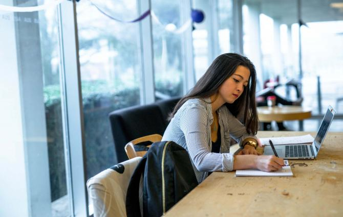 Student sitting at large table and writing on notepad