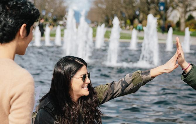students high fiving at the fountain