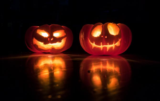 Two jack-o-lanterns in a dark room