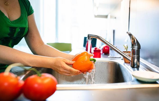 student washing a pepper in her dorm room