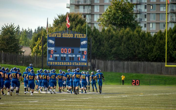 UBC Thunderbird football players running across the field
