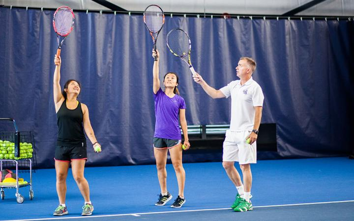 Two students learn tennis technique