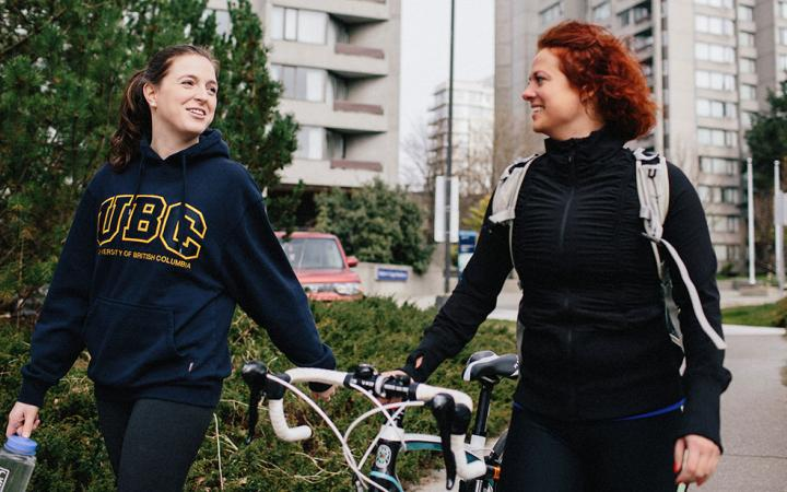Two students going for a walk with a bike
