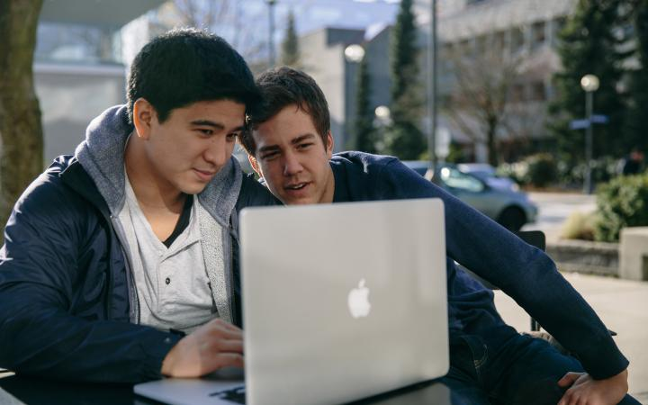 Two students sitting outside looking at a laptop screen