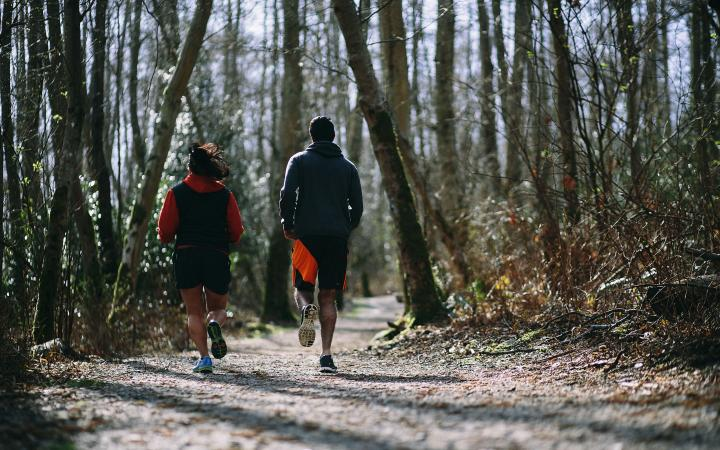 Students running through forest trails