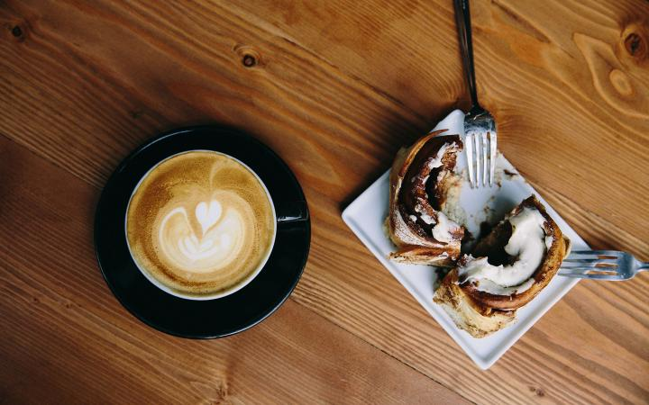 A coffee and cinnamon roll on a wooden table.