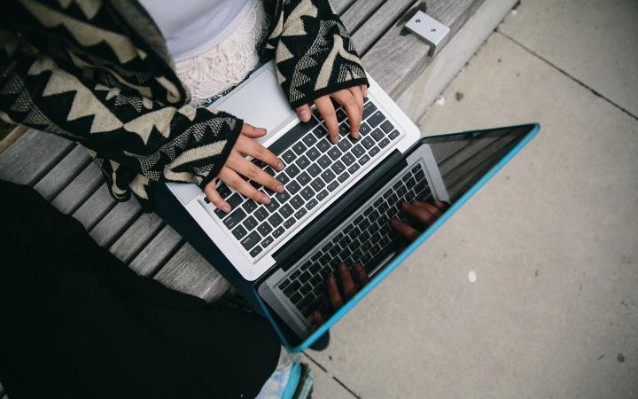 A student writing on a laptop