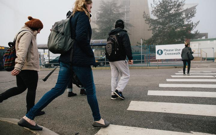 Students stepping onto the crosswalk at the bus loop
