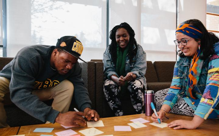 three students working with sticky notes