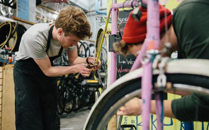 student fixing a bike