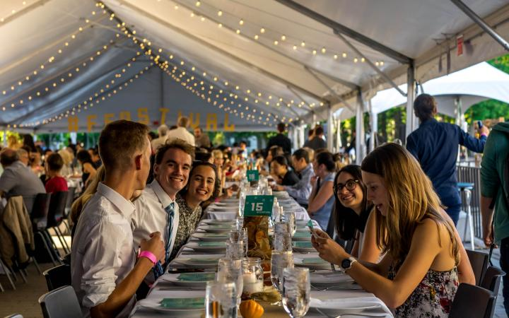 Students seated at long table for the Harvest Feastival