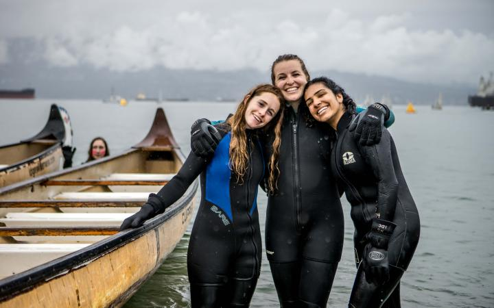 Three students in wetsuits hugging next to a longboat