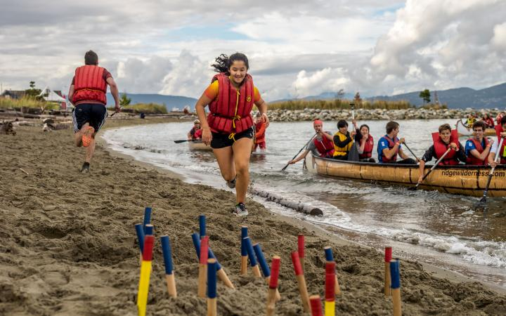A participant at Day of the LongBoat running out of the water to grab a baton in the sand.