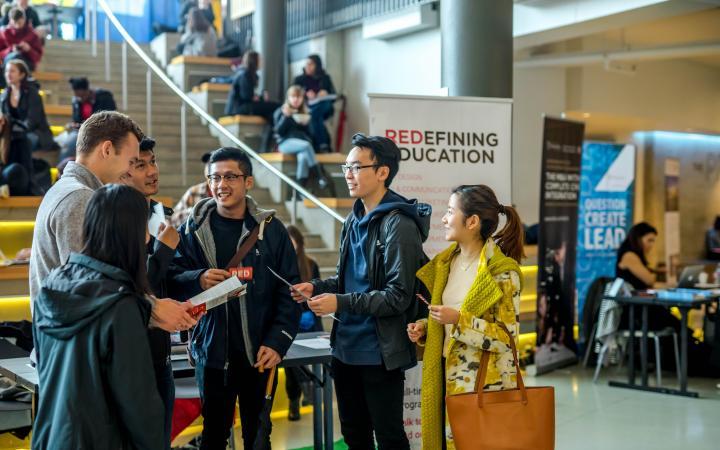 Students conversing at the Grad Fair