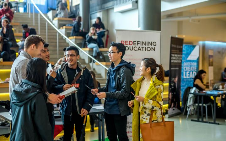 Students conversing at the Grad Fair