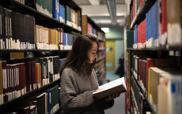 A student looking at books in Woodward.