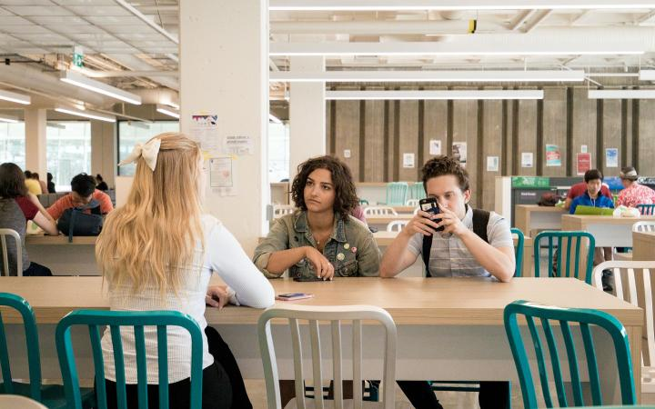 Two students having a conversation while the third student is on his phone
