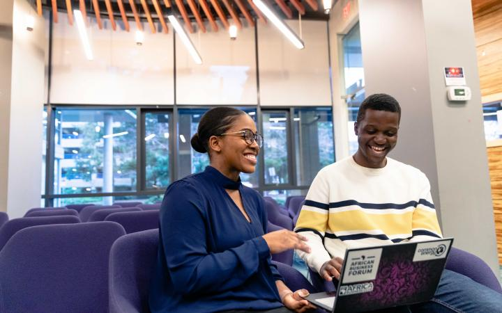two students laughing with a laptop