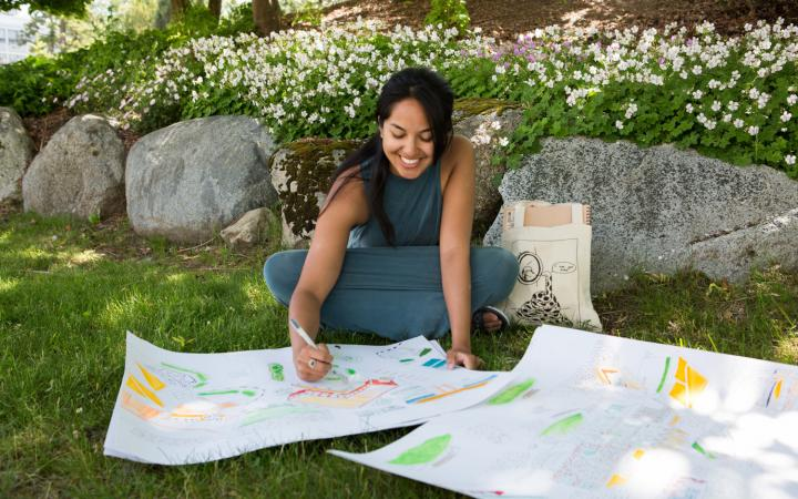 Sofia drawing on large sheets of paper in the grass