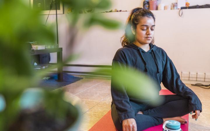 Student meditating at home