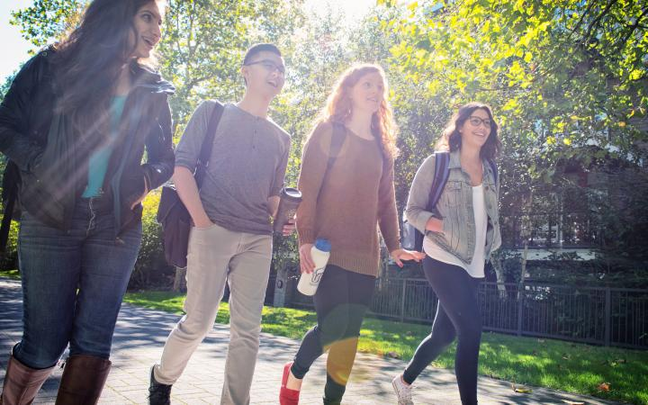 Four UBC students walking outside on campus