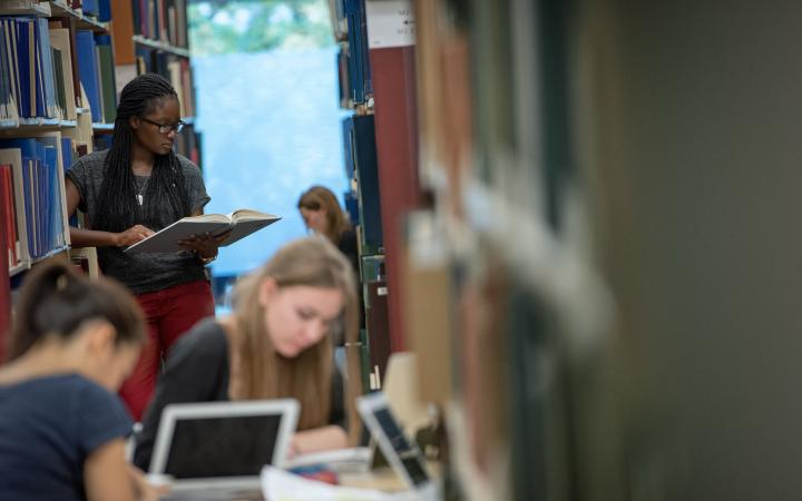 Students studying and browsing books in the library
