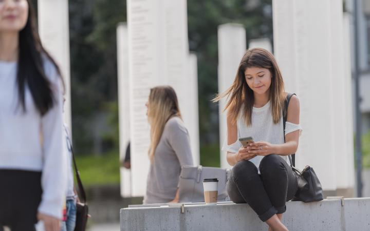 UBC student sitting outside looking at her phone