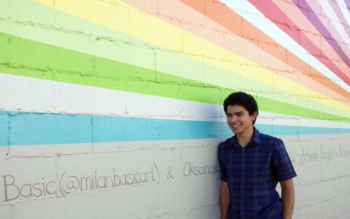 Carlos Doebeli, a UBC student, standing by a colourful, graphic wall
