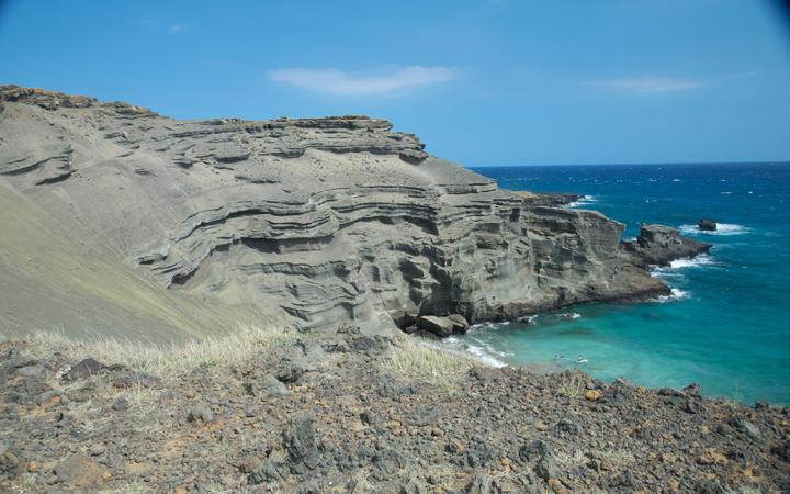 stratus rock formations on Hawaiian coast with bright blue water