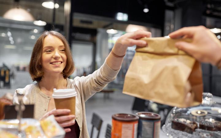 A student is smiling and reaching for her food purchase as she holds a cup of coffee