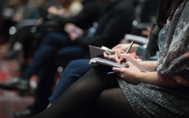 Students taking notes at a talk