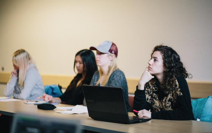 Four female students with laptops and papers in class, looking at the front.