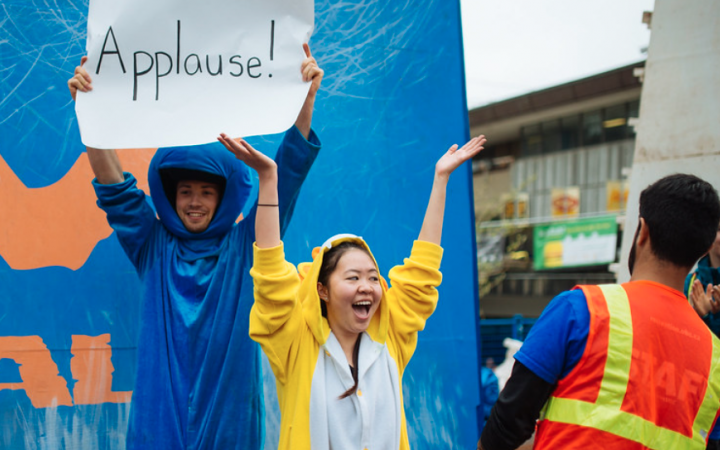 Two UBC students in animal onesies in front of Storm the Wall, with one student holding up a sign reading Applause.