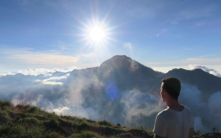 student on a landscape above the clouds, looking over the horizon