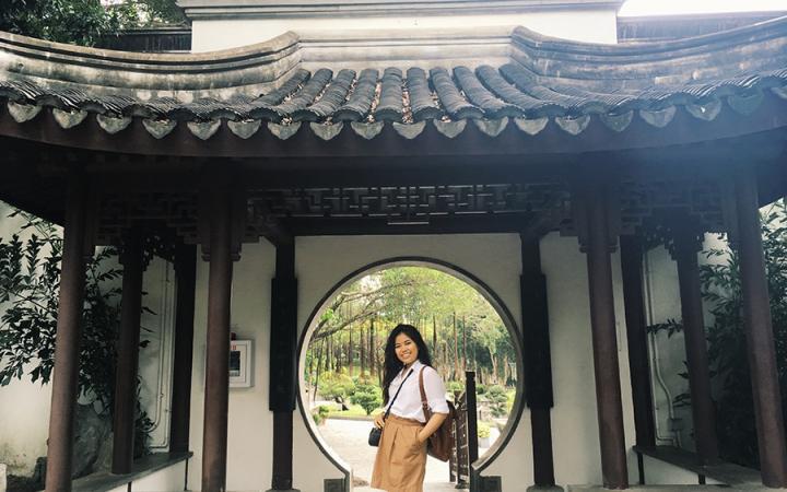 Sara posing in front of a circular door in Asia