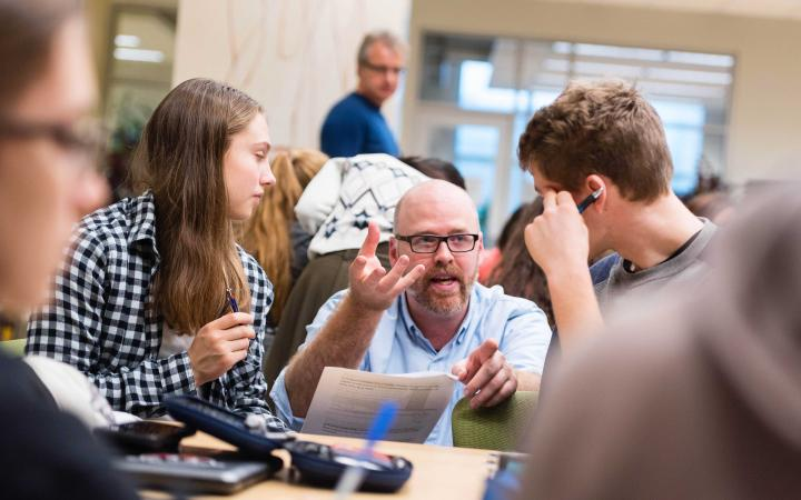 prof talking to students at a table