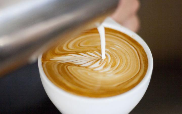 Someone pouring a latte