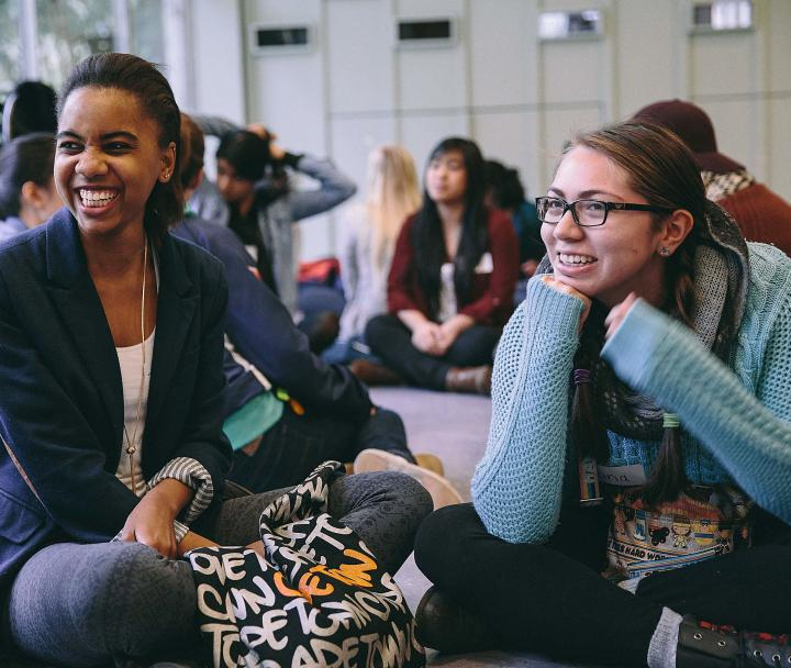Two female students sitting on the floor smiling