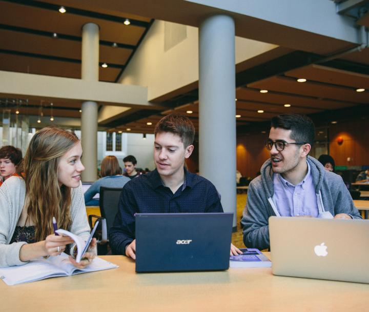 3 students talking at a table with laptops and notebook