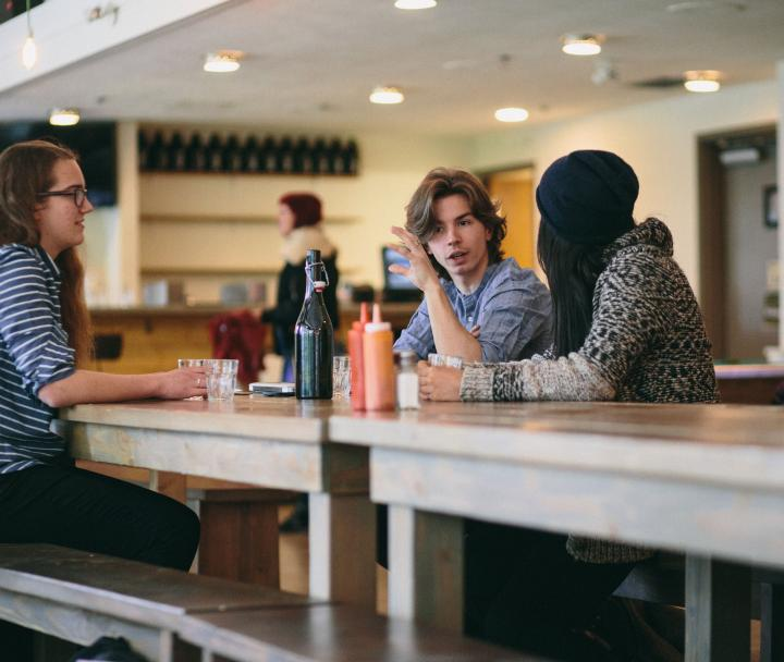 three students talking at a table