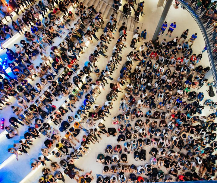 Crowd of students sitting on the floor of the Nest