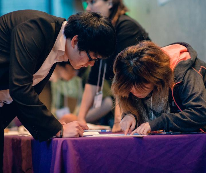 Two students at a registration table