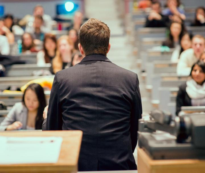 Presenter standing at the front of a lecture hall